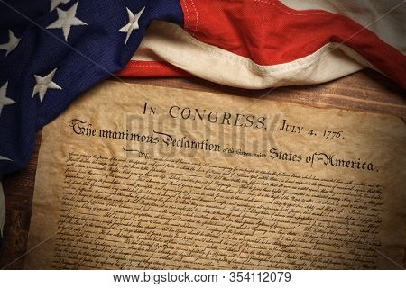 A copy of the United States Declaration of Independence with a vintage American flag on a wood background