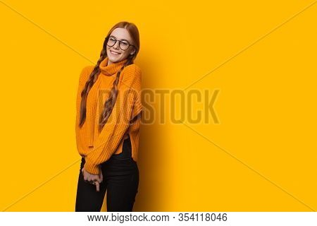 Charming Red Haired Caucasian Lady With Eyeglasses Is Smiling Happily And Posing Near Yellow Freespa