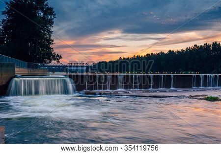 The Overflow At Penrith Weir As The Sunset Colours Some Of The Clouds In The Sky And Reflects In The
