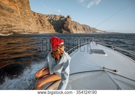 Young Woman Dressed Casually In Jacket And Red Hat Enjoying Sea Voyage, Sailing On A Yacht In Stormy