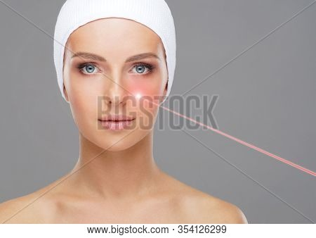 Doctor Removing Birthmarks With A Laser Ray. Beautiful Face Of A Young Woman. Mole Removal, Plastic
