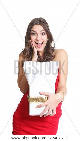 Surprised brunette with a gift in her hand