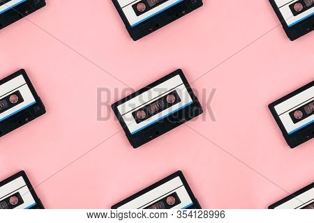 Seamless Pattern With Retro Audio Cassettes Flat Lay On Colorful Pink Background Top View. Creative