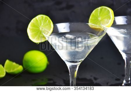 Two Glasses Of Martini With Lime On A Black Background. Two Glasses Of Martini Cocktail In A Bar