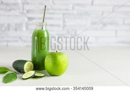 Bottle Of Detox Green Smoothie Made With Apple, Spinach And Cucumber On White Wooden Table. Superfoo
