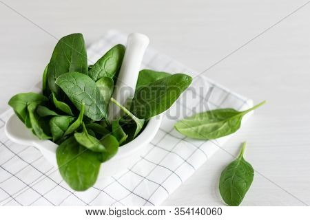 Green Spinach Leaves In Mortal Bowl On White Wooden Table. Healthy Eating Concept. Detoxification.
