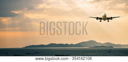 Passenger Airplane. Landscape With Front Of White Airplane Is Flying In The Orange Sky With Clouds O
