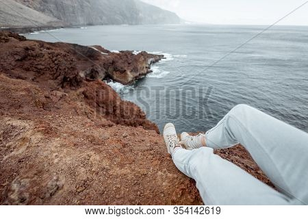 Traveler Sitting Above The Precipice On A Rocky Coast, Traveling On The Island, Cropped View, Focuse
