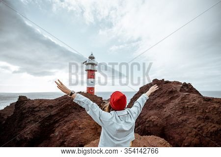 Carefree Stylish Woman Dressed In Jeans And Red Hat Enjoying Trip On A Rocky Ocean Shore Near The Li