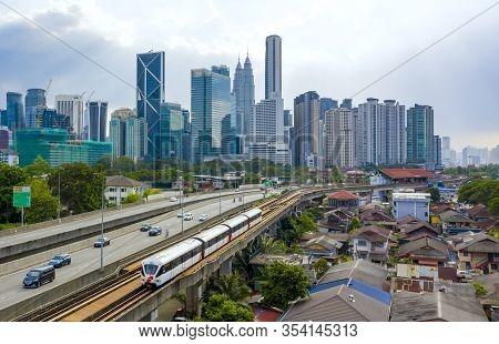 Kuala Lumpur Skyline With View Of Lrt Train