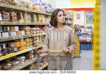 Serious Woman With Shopping Cart In Grocery Store. Attractive Young Woman Pushing Shopping Cart And