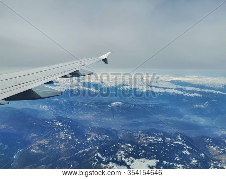 Flight From Germany To Venice. View Over Snow-covered Mountains In The Alps. Wing Of A Plane With Wi