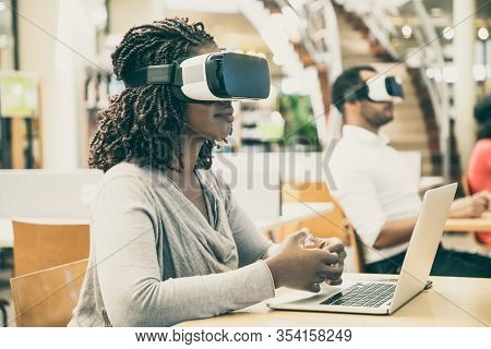 Adult Students Using Vr Simulators For Work On Project In Library. Man And Woman Wearing Virtual Rea