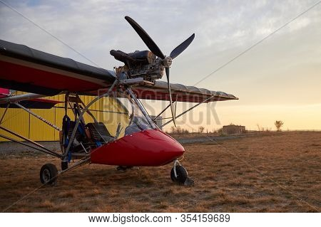 Ultralight Two-seater Airplane With A Propeller Stands On The Airfield Against The Background Of A H