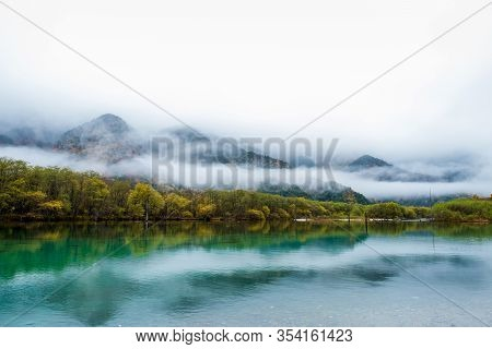 Kamikochi National Park In Autumn Season, Autumn Trees Reflection On Water Or Pond ,many Fog At Foot