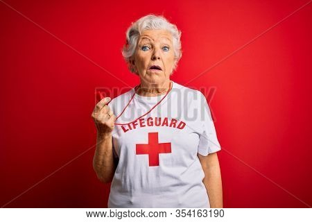 Senior beautiful grey-haired lifeguard woman wearing t-shirt with red cross using whistle In shock face, looking skeptical and sarcastic, surprised with open mouth