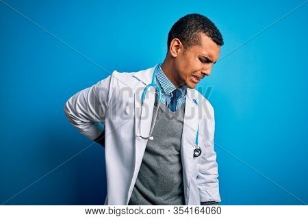 Handsome african american doctor man wearing coat and stethoscope over blue background Suffering of backache, touching back with hand, muscular pain