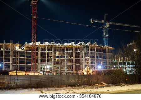 Night Construction Site At Dusk. Construction Crane In Night Illumination, The Construction Of A Mul