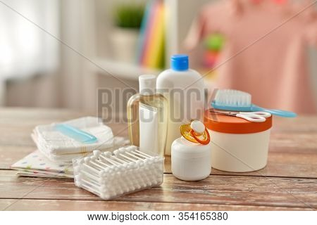 bath time and care products concept - baby accessories for bathing on wooden table at home