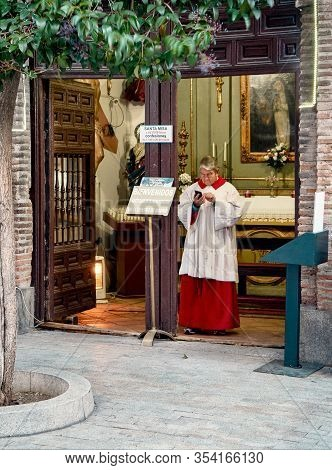 Madrid, Spain - March 4, 2020. An Older Priest Using A Celullar Phone At The Gates Of The Humillader