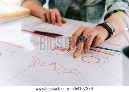 Close Up Of Accountant Hand Holding Pen Working On Calculator To Calculate Business Financial Report