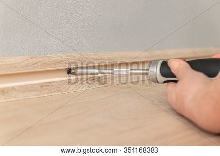 Worker Woman Manually Tightening A Screw In A Hole In The Wall With A Screwdriver. House Repair, Ins