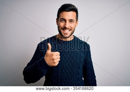 Young handsome man with beard wearing casual sweater standing over white background doing happy thumbs up gesture with hand. Approving expression looking at the camera showing success.