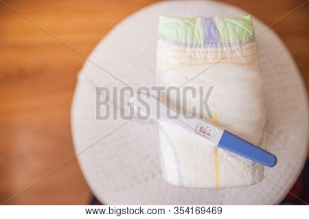 A Lot Of Diapers In A Stack Close-up And Copy Space. Diapers And A Positive Pregnancy Test. Newborn,