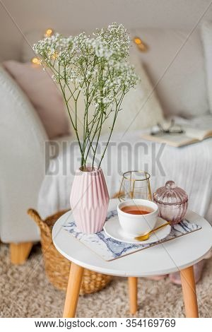 Spring Home Cozy Interior. A Bouquet Of Flowers In A Vase, A Cup Of Tea, Decor On A Coffee Table.