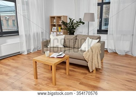 comfort, furniture and interior concept - sofa with cushions, coffee and book on table at cozy home living room