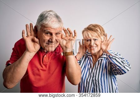 Senior beautiful couple standing together over isolated white background Trying to hear both hands on ear gesture, curious for gossip. Hearing problem, deaf