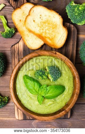 Ready To Eat Fresh Hot Broccoli Puree Soup With Slices Of Broccoli And Basil Leaves In A Wooden Plat