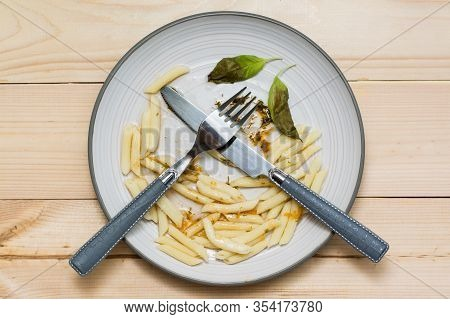 Stop Wasting Food. Leftover Lunch And Cutlery On A Plate On A Wooden Background. Food Waste Concept