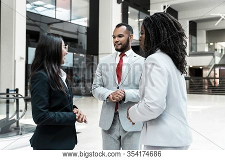 Agent And Clients Meeting And Discussing Deal In Office Hall. Business Man And Women Standing In Hal