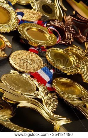 group of trophy and medals over blackboard background. top view. flat lay.Trophy is a specific achievement, serves as recognition / evidence of merit, awarded for sporting events