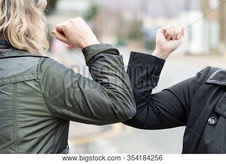 Elbow Bump. New Novel Greeting To Avoid The Spread Of Coronavirus. Two Women Friends Meet In A Briti