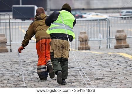 Electric Cable Laying, Workers Pull The Wire Along A City Street. Power Supply And Lighting, Repair