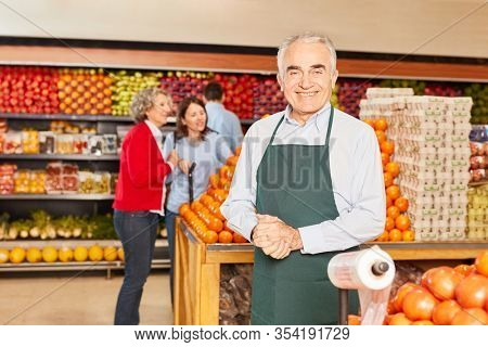 Senior man as a salesman or market manager in the vegetable department in the supermarket