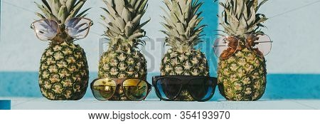 Closeup Of Group Of Fresh Pineapple Hipster Family In Funny And Stylish Sunglasses On Table Against