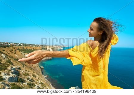 Happy Atractive Taned Woman Posing With Hand Reaching Out On Cliff Edge With Beautiful Sea View.