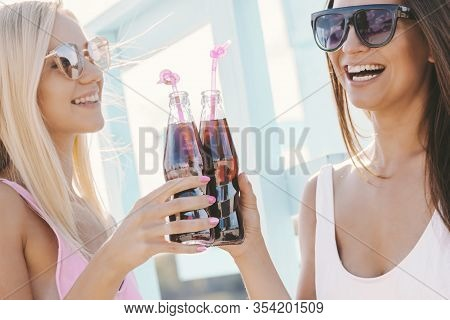Portrait Of Two Happy Girls Friends Drinking Cold Refreshing Lemonade And Laughing At Sunny Beach. B