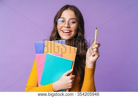 Image of young beautiful student girl wearing eyeglasses smiling and holding exercise books isolated over violet background