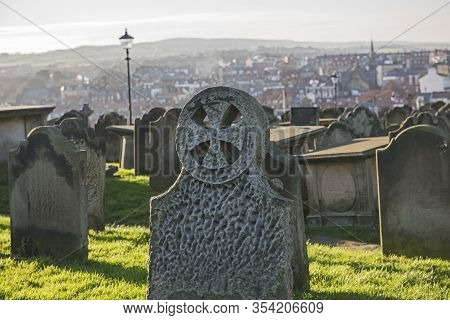 Old Eroded Church Cemetary Graveyard With Rows Of Headstones And Tombs In Rural Landscape