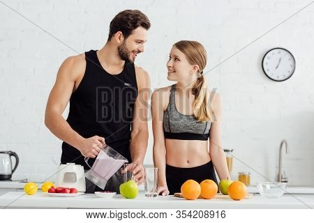 Sportive Man Pouring Smoothie In Glass Near Happy Woman And Fruits