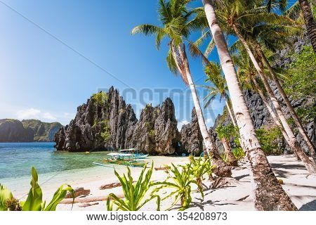 Hidden Beach With First Tourist Trip Boats In Morning Sun Light At El Nido, Palawan, Philippines