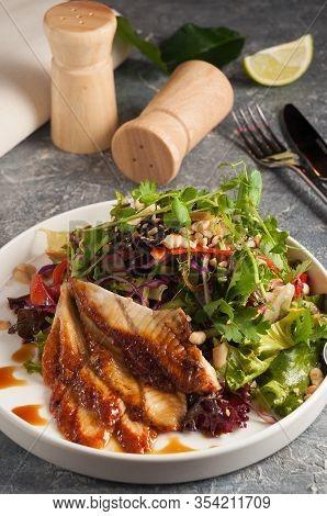 Japanese Cuisine - Chuka Seaweed And Unagi Smoked Eel Salad With Nuts Sauce. Topped With Eel Sauce A