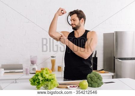 Handsome And Sportive Man Measuring Muscle On Hand Near Fresh Food