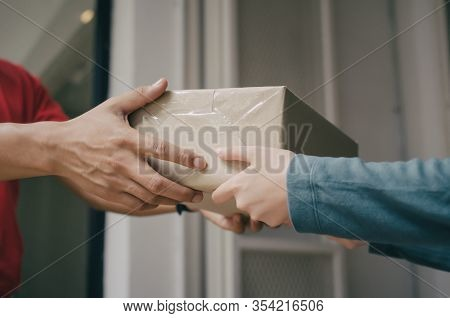 Hand Of Delivery Service Man In Red Uniform With Woman Customer Receiving Parcel Post Box From Couri