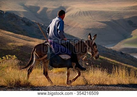 Dushanbe, Tajikistan. August 06, 2019. A Peasant On A Donkey Rides Along The Pamir Highway On His Ow