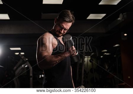 A Man With An Effort Does An Exercise For Biceps And Triceps With A Dumbbell. Embossed Bodybuilder.